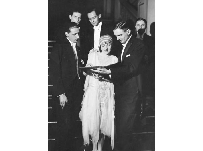 Aktorka Maria Malicka otoczona grupą mężczyzn. Za artystką stoi aktor Zbigniew Sawan (1929), zbiory Narodowego Archiwum Cyfrowego