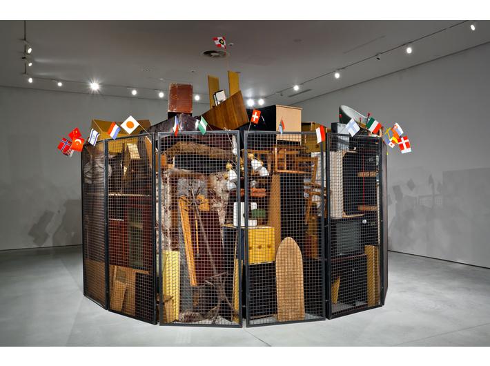 Jarosław Kozłowski, //Zjednoczony świat – wersja totalitarna//, 2000, instalacja / stalowe kraty, meble, akcesoria AGD, flagi, Ø około 5 m, Kolekcja MOCAK-u, fot. R. Sosin