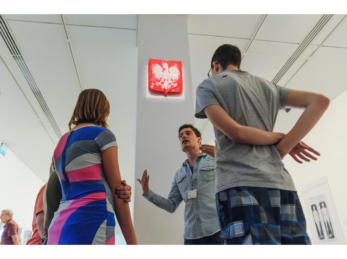 Oprowadzanie po wystawie //Ojczyzna w sztuce// w MOCAK-u. W tle na filarze praca Bartosza Muchy //Godło// (2006), fot. L. Radyk