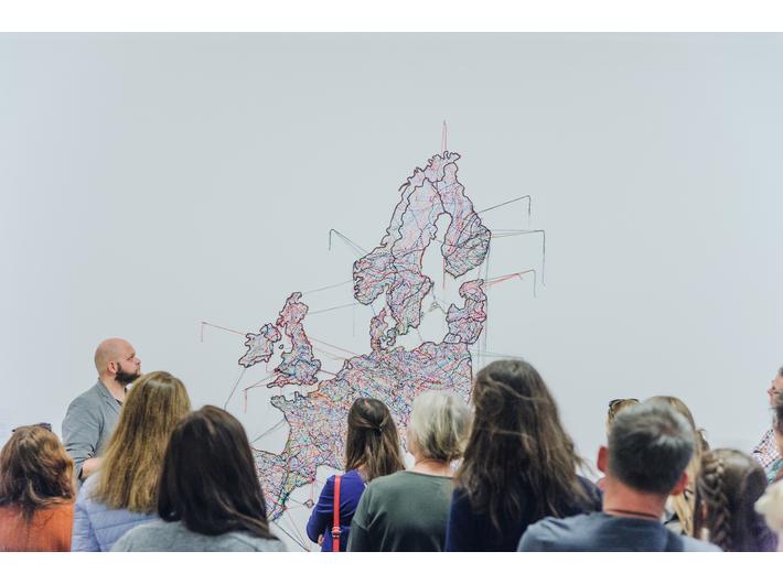 Oprowadzanie po wystawie //Ojczyzna w sztuce// w MOCAK-u. W tle praca Małgorzaty Markiewicz //Mapa// (2013), fot. L. Radyk